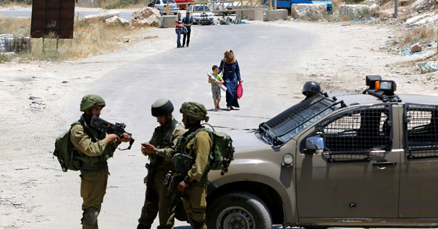 Israeli soldiers stand guard at the entrance of Yatta