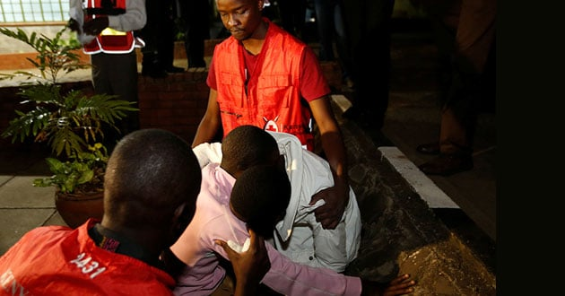 Kenya Red Cross staff members console relatives of the civilians killed in an attack at the Bisharo lodging by Islamist militants