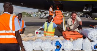 Workers unload the rolled tarps and hygience kits from Samaritan's Purse