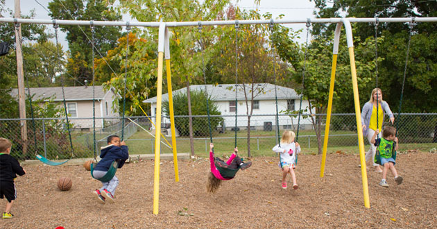 Children play on a gravel paved playground