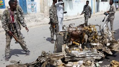 Soldiers walk around the wreckage of a car bomb in Somali