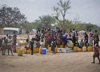 Children and women displaced by recent fighting in South Sudan gather near jerry cans and other water supplies in the town of Mingkaman, where humanitarian assistance is being provided.  Photo © UNICEF/NYHQ2014-0359/Holt.